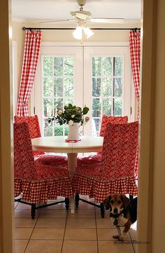Pretty red and white dining room! Red buffalo check curtains, Ikea Liatorp dining table, & red slipcovered chairs