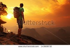 Hiker with backpack standing on top of a mountain and enjoying sunrise by Dudarev Mikhail, via Shutterstock