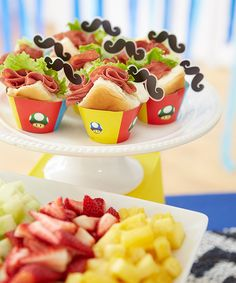 Mini sandwiches look great when creatively presented, and a display of fresh fruit — we sliced strawberries then added pre-cut chunks of pineapple and melon purchased from a grocery store — rounds out the meal.