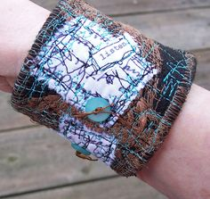 Fabric Cuff Bracelet created with handpainted cheesecloth, handwritten graffiti, free motion stitching and hand-tied buttons on a base of black felt.