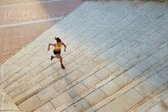 Stocksy United – Royalty-Free Stock Photos – Fast runner on steps in sunlight by Guille Faingold Urban Fitness, Barcelona, Sunlight, Sidewalk, Royalty Free Stock Photos, Louvre, The Unit, Building, Travel