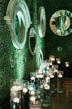 Various mirrors on walls covered in greenery and countless floating candles create a magical secret garden indoors.