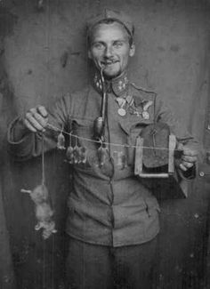 WWI Austrian soldier with trench trophy of a rat and her pups.