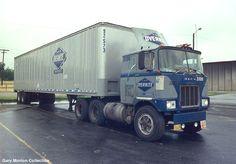Overnite Transportation Mack Model F pulling a ribbed semi trailer.