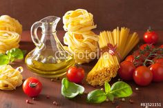 raw pasta olive oil tomatoes. italian cooking in rustic kitchen