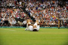 Roger Federer falls to the ground after winning match point against Andy Murray and claiming his seventh Wimbledon title. - Tom Lovelock/AELTC