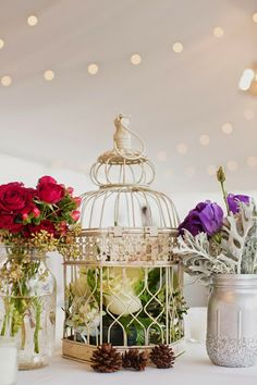 Winter wedding decor. Vintage and rustic style. Silver painted mason jars with dusty miller and purple flowers. Red roses in glass mason jars and gold painted bird cage with floral and pine cones. #gingerlilyevents #atlantaflorist #wedding #barnesleygarden