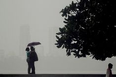 An Indian couple shelter under a umbrella during heavy rain showers in Mumbai on Sept. 3. The monsoon rains, a key to India's economy, covered the entire country on July 11 but it was 23 percent below average, officials said amid worries of its impact on two cereal-producing states. (Punit Paranjpe/AFP/Getty Images)