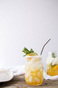 Minimal photo showcasing the Peach Tea Bourbon Smash with stainless steel straw and white back drop