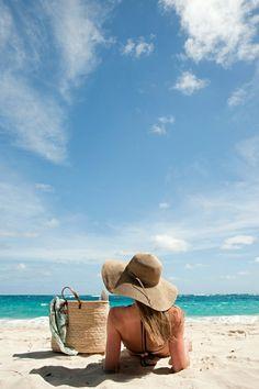 un grand sac de plage en paille beige, femme allongé au bord de la mer