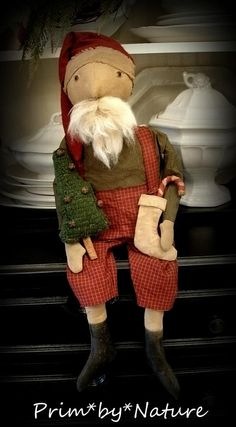 Primitive Santa from osnaburg - stitched features and real sheep's wool for his beard - red and white checked overalls and a mini checked green fabric shirt. His hat is dark red flannel - His boots are painted black - He is holding an 8 1/2 inch hooked wool Christmas tree from green wool - with bells and a cinnamon stick trunk - He has a 6 1/2 inch raggedy candy cane placed in a stocking that I made for him from stained cotton - the stocking is 4 1/2 inches tall