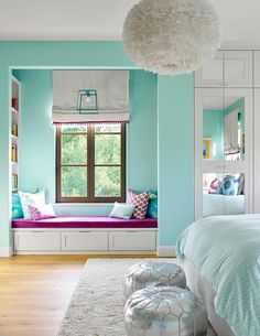 Turquoise blue girl's bedroom features a white feather chandelier, Eos White Pendant, illuminating a white bed dressed in pale blue bedding.