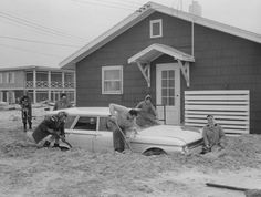 Digging sand ( Baltimore Sun photo by Aubrey Bodine / April 15, 1962 ) People dig sand away from a car after the 1962 flood in Ocean City, Maryland.