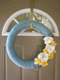 Gray, white and yellow felt flowers on a yarn wrapped wreath. Good tutorial and a fun project.