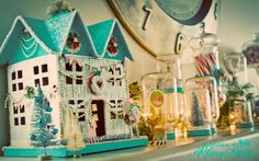 paper holiday house, handmade snow globes and candy filled apothecary jars. Christmas mantel perfection.