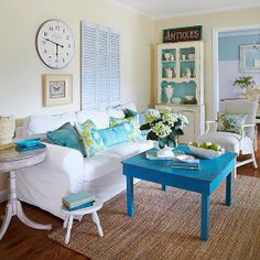 BHG:  Painting an old brown card table with cerulean aqua paint brought a splash of bold color and repeating a bold hue in a space filled with softer colors brings unity and makes the standout color look like it belongs. Here, the watery cerulean is repeated on the solid throw pillows and the back of the china cabinet. A collection of antiques, flea market finds, and castoffs complete the cottage look. A white slipcover on the sofa imbues casual cottage style in the room.