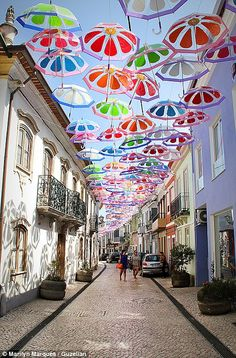 What a bright idea! Umbrellas unfurled above Portuguese street shower color onto people below      Umbrellas suspended across street are now a popular attraction     As well as brightening the street, they offer shade from summer sun     Idea has attracted tourists from all over the world to Agueda in Portugal