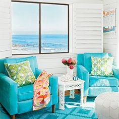 Bold turquoise defines this living room. Anya Sarre introduced vibrant rugs and chairs that set the tone in an otherwise all-white room. | Coastalliving.com