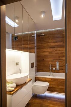 W łazience na podłogach i ścianie dominuje ciepłe drewno.