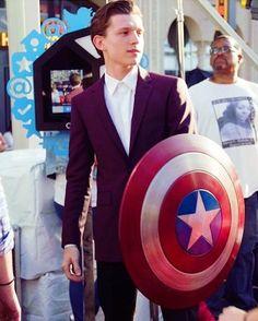 Tom Holland holding Cap's shield
