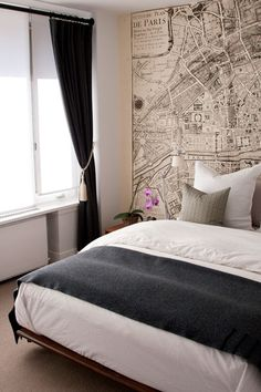 Beautiful city bedroom design with vintage map wallpaper, modern platform bed, gray flannel blanket, taupe pillows and black velvet curtains.