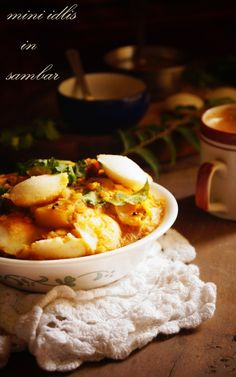 Mini Idlis in Sambar Recipe. Soft fluffy mini idlis dunked in ghee laden flavourful sambar. I was introduced to this dish at Saravana Bhavan when I came to M...