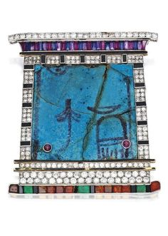 An Egyptian Revival 'Pylon' Brooch, Cartier, London, circa 1923. Designed as the entryway to an Egyptian temple, the glazed faience plaque framed with round, old European and single-cut diamonds, accented by channel-set and calibré-cut rubies, sapphires, citrines, emeralds, and amethysts, further set with cabochon rubies and onyx segments, the faience plaque backed with gold, with enamel accents, mounted in platinum, signed Cartier, Londres, numbered. #Cartier #EgyptianRevival #brooch