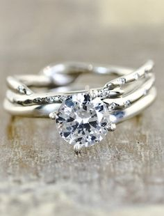 I think I really like the delicate twig/branch band ; maybe just two? Would like to see with an oval stone