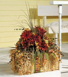 A fall flower arrangement with a barrel of hay adds warmth to a front porch!
