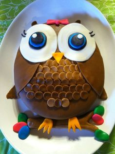 Owl cake I made for Kensleigh to match celebrate express's owl birthday supplies.  I will tell you the best I can. I am not a professional, just a mom who loved the owl theme. I live way out in the country and we don't have bakeries here, so I gave it a shot. This was my first attempt. I made the marshmallow fondant from wilton.com. It isn't easy to work with but it taste so much better then store bought. Anyway if you are going to make your own then do it at least 24 hrs. previous. Then you…