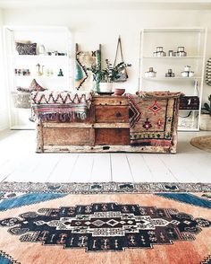 Rugs, rugs and more rugs! A bohemian atmosphere created by these amazing tribal rugs, especially the centre piece and the old wooden furniture. Plants always complete a bohemian look.