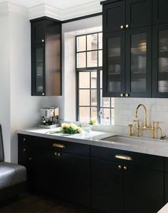 Black kitchen features glass reeded upper cabinets and black lower cabinets adorned with polished brass hardware paired with white marble countertops and a white subway tile backsplash.