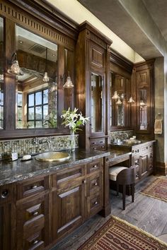 Detailed wooden cabinets provide plenty of storage space in this bathroom, and are brought to life by the rich wood grain. The matching floor is offset by the area rugs, and large windows to the rear flood the room with natural light.