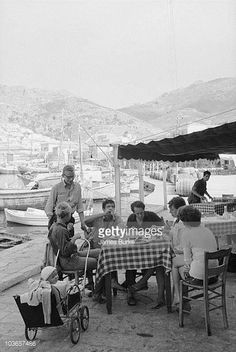 Leonard Cohen eating with Marianne Ihlen her partner Axel Jensen and artist friends Hydra Greece October 1960 Marianne's son Axel is in the baby...