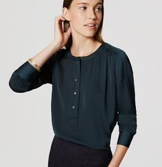 Sleekly designed with a wider button placket, this versatile piece makes an endlessly modern statement. Round neck. Long sleeves with button cuffs. Henley button placket. Shirred beneath shoulders and back yoke. Shirttail hem.
