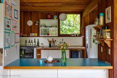 Cozinha integrada à sala com vista para o verde e mesa revestida de fórmica azul.