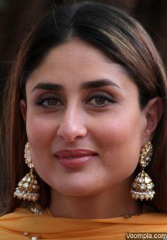 Kareena Kapoor's green and brown eyes dazzle in this gorgeous picture. The actress is photographed in a traditional look, complete with elaborate jhumkis and a yellow dress. via Voompla.com
