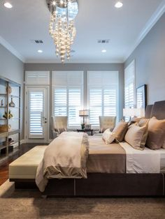 Jonathan Scott's calming bedroom includes a wall of windows and a door to the patio. A dazzling chandelier adds a touch of glam to the neutral space.