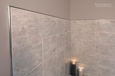Bathroom remodel by Renovisions. Contemporary style, chrome fixtures, tile tub surround, metal edging, grey tile