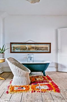 Colour is injected into this bathroom through the placement of a bright orange and pink shag rug in front of the freestanding bathtub. From 'Big Ideas', a story on page 162 of Vogue Living May/June 2012. Photograph by Eric Morin.