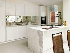 îlot de cuisine en marbre blanc avec une plaque de cuisson noire et une hotte…