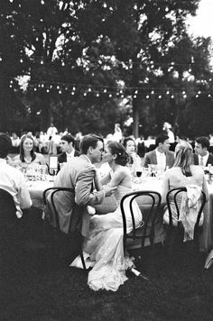 Romantic outdoor wedding reception - bride and groom first kiss under moonlight