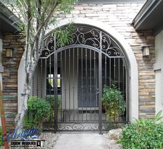 Arched wrought iron entryway with scrolls, knuckles and twisted pickets