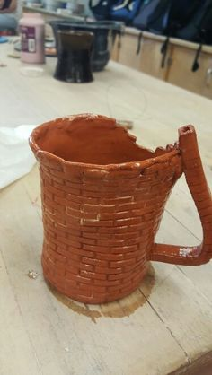 Texture assignment mug. Used brick patterned texture mat to form slab and hand-build this mug. Some white sig was used to highlight the brick texture. Red sig was used on the bottom. The entire mug is covered in lo-fire clear glaze. The clay is lo-fire red.
