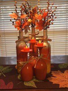 Cheap Fall décor. $ Tree wine glasses painted orange; $ Tree battery operated orange tea lights; wine bottles painted like candy corn; $ Tree silk flowers and twigs.