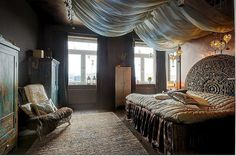Amazing ornate, carved, round wooden headboard and turquoise painted distressed antique wardrobes.  Interesting canopy.