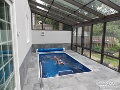 Pool enclosures make an affordable option for year-round swimming in a sunroom environment. When the light is right, the overhead panels will make a clever backstroke mirror for this swimmer! This Original Endless Pool, located in Rochester, New York, features our spa rail (front, left) for easy access and our Manual Retractable Security Cover (rear) to affordably control humidity and help maintain water temperature.