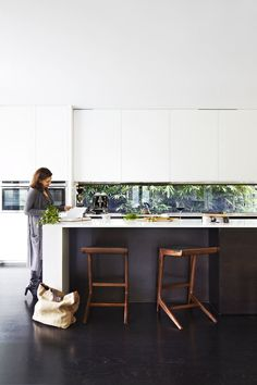 """Kylie at the long Corian benchtop, which affords her ample working space. To the right of the bench is a concealed butler's pantry. """"With the amount of entertaining we do, it's wonderful to have a designated place for mess,"""" she says. Stools, Clickon Furniture. Flooring, American oak with a black japan finish. Australian House & Garden"""