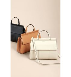 A subtle, modern take on a Tory Burch logo elevates a structured top-handle satchel shaped from fine-grain leather.
