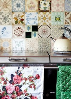 Floral teatowel hangs on Aga with kettle and tiled splashback in Oxfordshire kitchen England UK